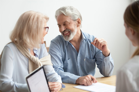 A smiling, soon-to-be retired couple sit across the table from a retirement advisor to discuss strategies for retirement.