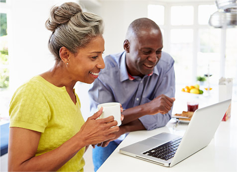 A soon-to-be retired couple using a laptop computer in their kitchen to search online for a retirement planner.
