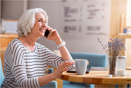 A woman on the phone smiling and considering her options with her advisor before deciding when to take Social Security.